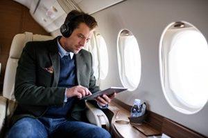 businessman on plane wearing headphones looking at tablet