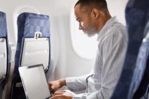 man using laptop on airplane