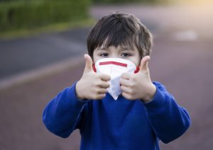 boy wearing mask and giving thumbs up during corona virus