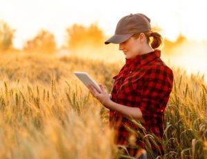 woman in field on tablet device
