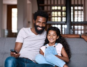father and daughter watching tv in subsahara africa